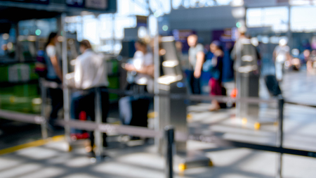 Blurred photo of people standing in line to flight check-in in airport