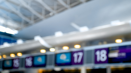 Out of focus photo of display on top of flight check-in zone in airport terminal Stock Photo