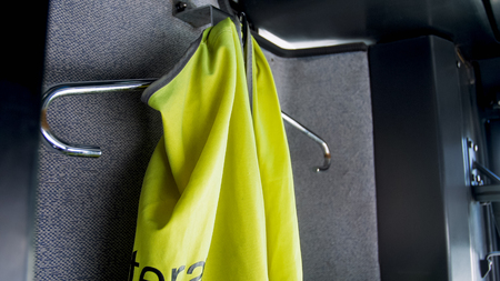 Closeup photo of green safety vest hanging on hanger at passenger bus