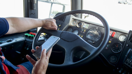 Closeup photo of irresponsible man typing phone number while driving truck. Danger in transport. Irresponsible driver