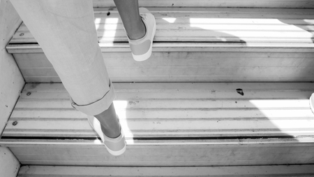 Black and white photo of female feet on airplane doard stairs Foto de archivo - 109313412