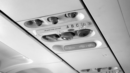 Black and white photo of passenger control panel on the ceiling of jet airplane