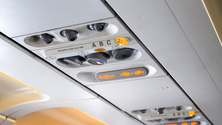 Closeup photo of air conditioner holes and and individual lights over the passenger seat of aircraft