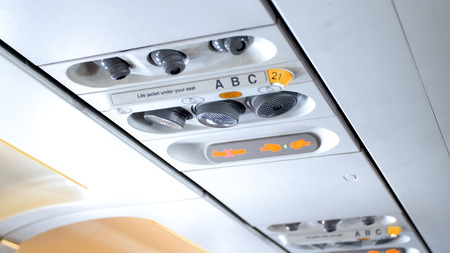 Closeup photo of control panel with emergency signs and air conditioner system in modern airplane