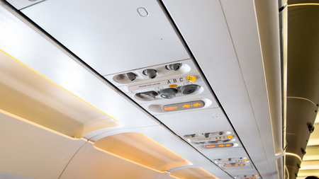 Closeup photo of control panel on ceiling of passenger jet airplane