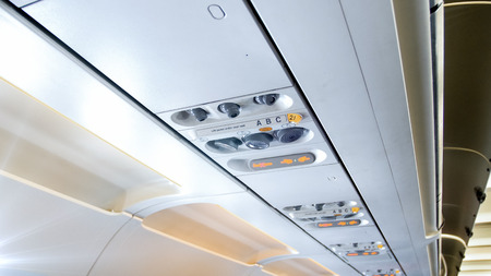 Closeup photo of fasten seat belts sign and air vents above the passenger seat