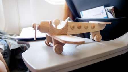 Closeup photo of wooden toy airplane on foldable table at aircraft Stock Photo
