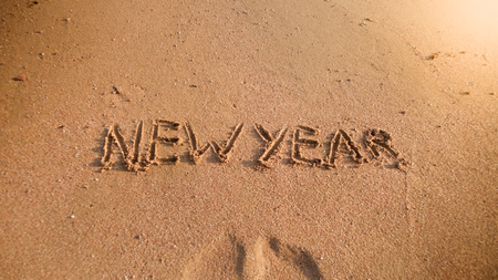 Closeup image of words New Year written on wet sand on the sea beach. Concept of winter holidays, Christmas and tourism