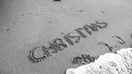 Black and white image of word Christmas written on wet san on the beach. Sea wave flowing over. Concept of winter holidays, New Year and tourism