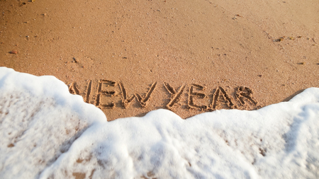 Closeup image of sea waves rolling over words New Year written on wet sand on the beach. Concept of winter holidays, Christmas and tourism