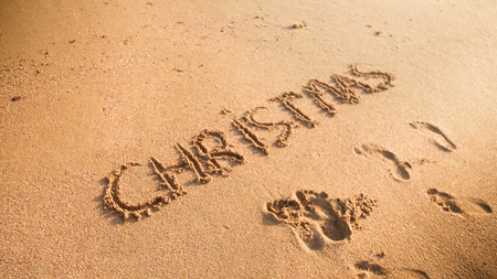 Closeup photo of word Christmas inscripted on sandy beach. Footaprints on wet sand. Concept of winter holidays, New Year and tourism
