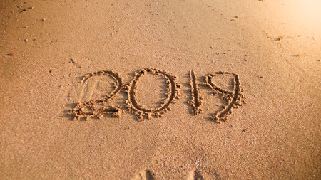 2019 New Year written on wet sand on ocean beach. Concept of winter holidays, Christmas and tourism Stock Photo