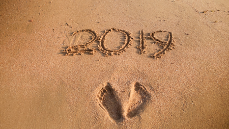 Closeup image of 2019 New Year numbers and footrpints on wet sand at ocean beach. Concept of New Year, Christmas and travel on winter holidays.