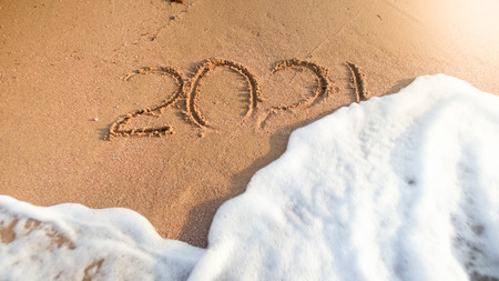 Closeup photo of 2021 numbers being washed from wet sand on beach by the sea wave. Concept of New Year, Christmas and travel on winter holidays. Stock Photo