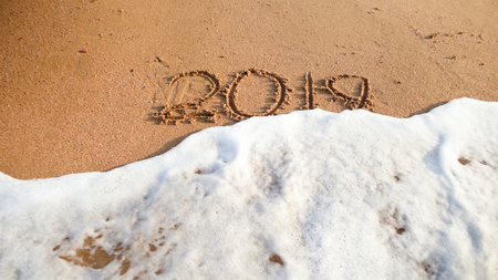 Closeup image of sea waves rolling over 2019 numbers written on wet sand at beach. Concept of New Year, Christmas and travel on winter holidays. Stock Photo