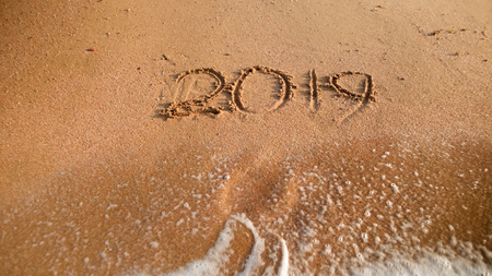 Closeup photo of sea waves washing 2019 new year numbers from sand on the beach. Concept of New Year, Christmas and travel on winter holidays. Stock Photo
