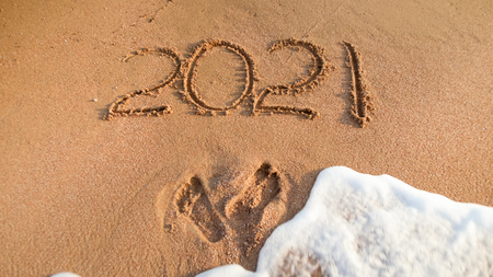 Closeup photo of 2021 numbers written on sand and footprints on sea beach. Concept of New Year, Christmas and travel on winter holidays. Banco de Imagens