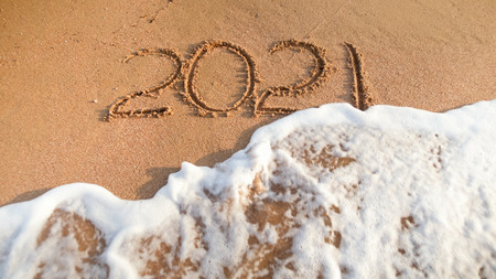 Photo of sea wave washing out 2021 numbers written on wet sand at beach. Concept of New Year, Christmas and travel on winter holidays.