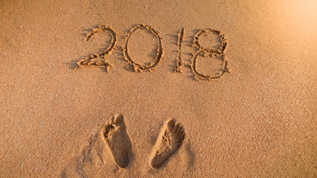 Closeup photo of footprints next to 2018 New Year numbers written on wet beach sand. Perfect image to illustrate Christmas, winter holidays, travel and tourism.