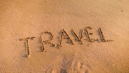 Closeup image of word Travel inscripted on the sand at beach. Concept of tourism, traveling, trips and journeys. Stock Photo