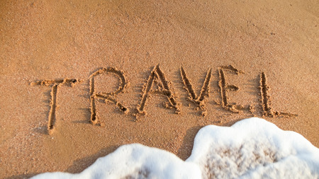 Closeup photo of sea waves washing off word Travel written on beach sand. Concept of tourism, traveling, trips and journeys.