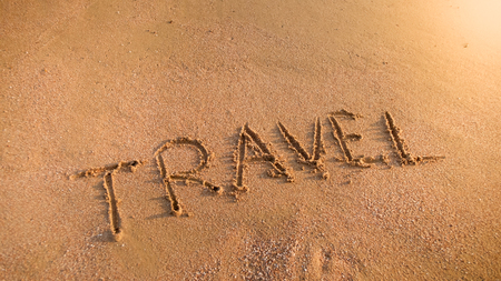 Photo of word travel inscripted on wet sand on the ocean beach at sunset. Concept of tourism, traveling, trips and journeys.