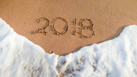 Closeup image of ocean waves rolling over 2018 numbers written on wet sand. Concept of celebrating and traveling on winter holidays.
