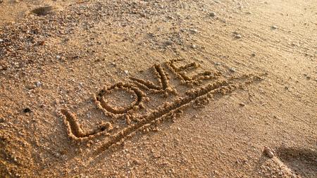 Closeup photo of word love written on wet sand at beach