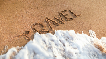 Closeup image of ocean waves rolling over word travel written on wet sand. Concept of tourism, traveling, trips and journeys.