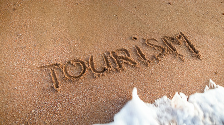 Closeup photo of ocean waves rolling over word toruwism written on wet beach sand. Concept of tourism, traveling, trips and journeys. Stock Photo