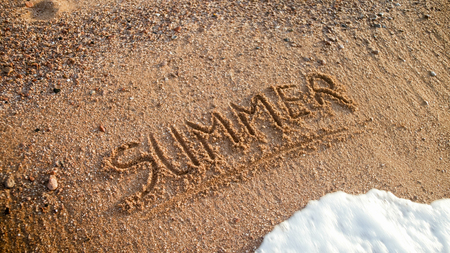 Closeup photo of word summer written on wet beach sand. Concept of tourism, traveling, trips and journeys.