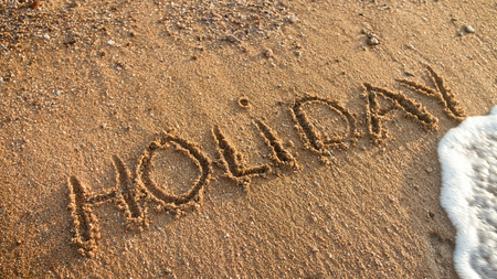Closeup image of sea waves rolling over word holiday written on beach sand.