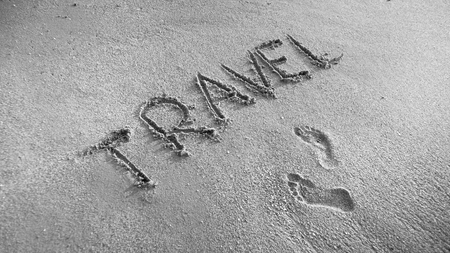 Black and white photo of two footprints and word Travel inscripted on wet beach sand