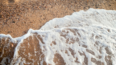 Closeup photo of ocean waves rolling over sandy beach at sunset Stock Photo