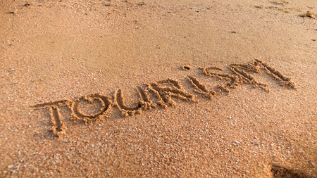 Closeup image of word tourism inscripted on wet beach sand. Concept of tourism, traveling, trips and journeys.