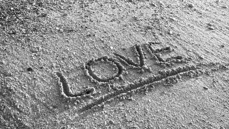 Black and white photo of word love written on wet beach sand