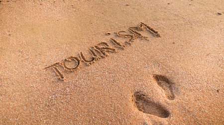 Closeup image of two footprints and word tourism written on wet beach sand Stock Photo
