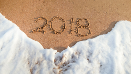Closeup image of 2018 New Year written on wet sand on sea beach. Concept of celebrating and traveling on winter holidays.