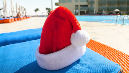 Closeup image of Santa cap lying on the matress next to the swimming pool. Concept of travel and tourism on Christmas, New Year and winter holidays.