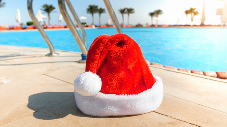 Closeup image of Santa Claus hat lying at the poolside in summer resort. Concept of travel and tourism on Christmas, New Year and winter holidays.