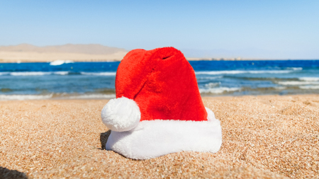 Santa Claus hat lying on the sand at sea beach. Concept of travel and tourism on Christmas, New Year and winter holidays. Stock Photo