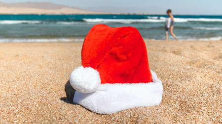 Closeup photo of red Santas hat on beach against relaxing tourists. Concept of travel and tourism on Christmas, New Year and winter holidays.