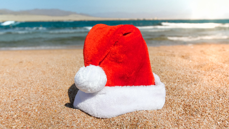 Closeup image of Santa Clauss hat against ea waves on beach at sunny day. Concept of travel and tourism on Christmas, New Year and winter holidays.