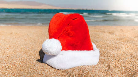 Closeup image of Santa Claus left his hat on the sand at sea beach. Concept of travel and tourism on Christmas, New Year and winter holidays.
