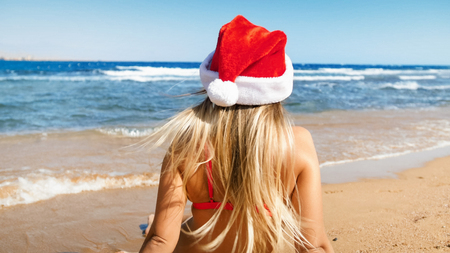 Rear view photo of young woman in long hair wearing Santa Clauss hat looking at the sea. Concept of travel and tourism on Christmas, New Year and winter holidays.