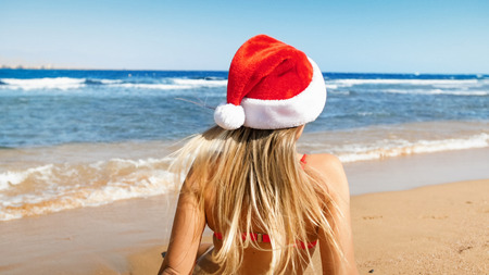 Rear view photo of young woman with long hair wearing Santa Claus cap sitting on the beach. Concept of travel and tourism on Christmas, New Year and winter holidays. Stock Photo