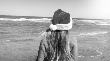 Black and white photo of young woman wearing Santas hat sitting on th ebeach and looking at sea. Concept of travel and tourism on Christmas, New Year and winter holidays. Stock Photo