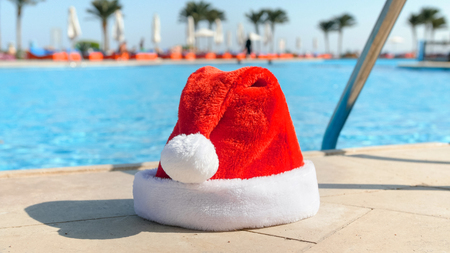 Photo of red Santa cap lying next to the swimming pool at summer resort. Concept of travel and tourism on Christmas, New Year and winter holidays.