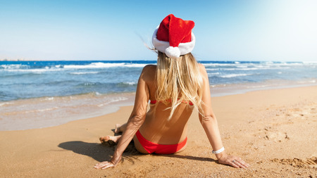 Rear view image of young woman wearing Santas hat relaxing on the sea beach. Concept of travel and tourism on Christmas, New Year and winter holidays.