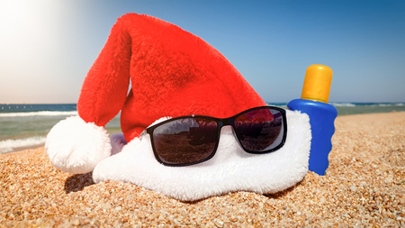Closeup photo of Santa Claus hat with sunglasses and sunscreen lotion lying on the beach. Concept of travel and tourism on Christmas, New Year and winter holidays. Stock Photo